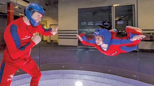Man helping boy in skydive chamber