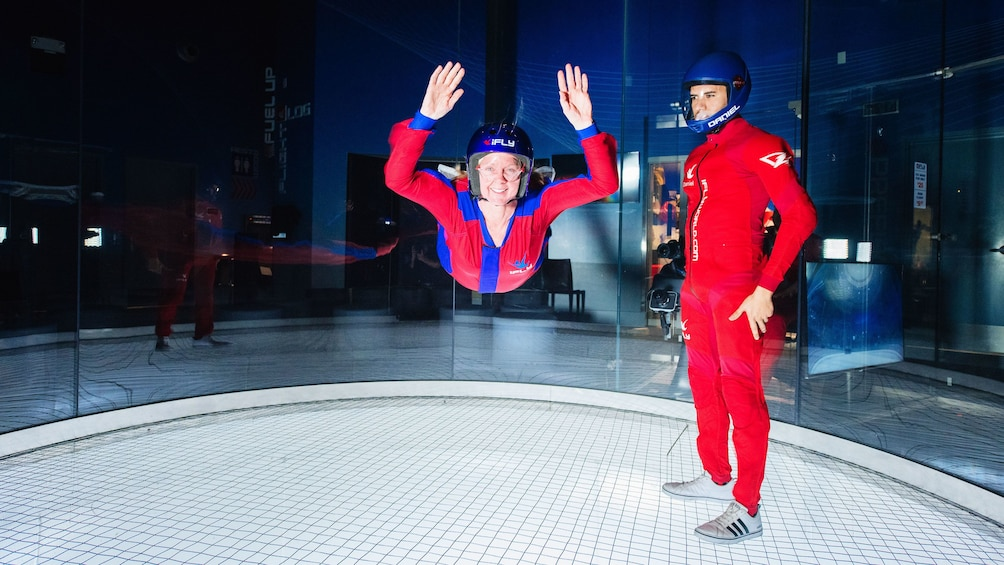 Cargar foto 3 de 5. Woman flying next to instructor in iFly