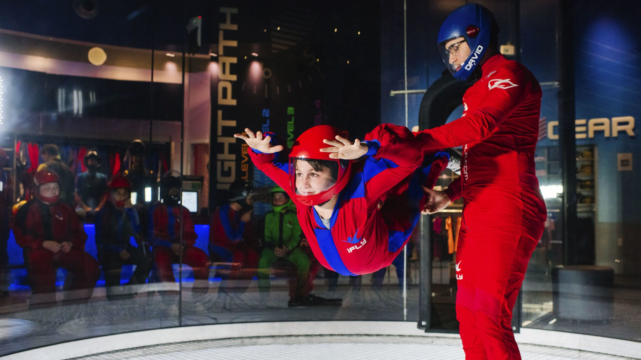 Child flying in indoor skydiving room at iFLY