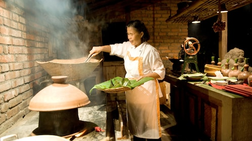 woman cooking in large pan in bali
