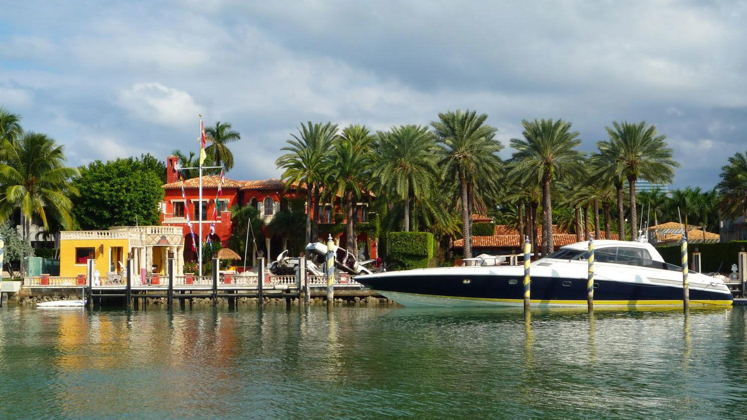 A boat docked infront of a mansion in Miami