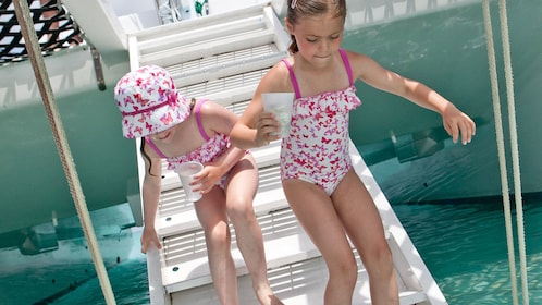Two girls swimming on the Sesame Sail Away Catamaran Cruise in the Turks and Caicos Islands