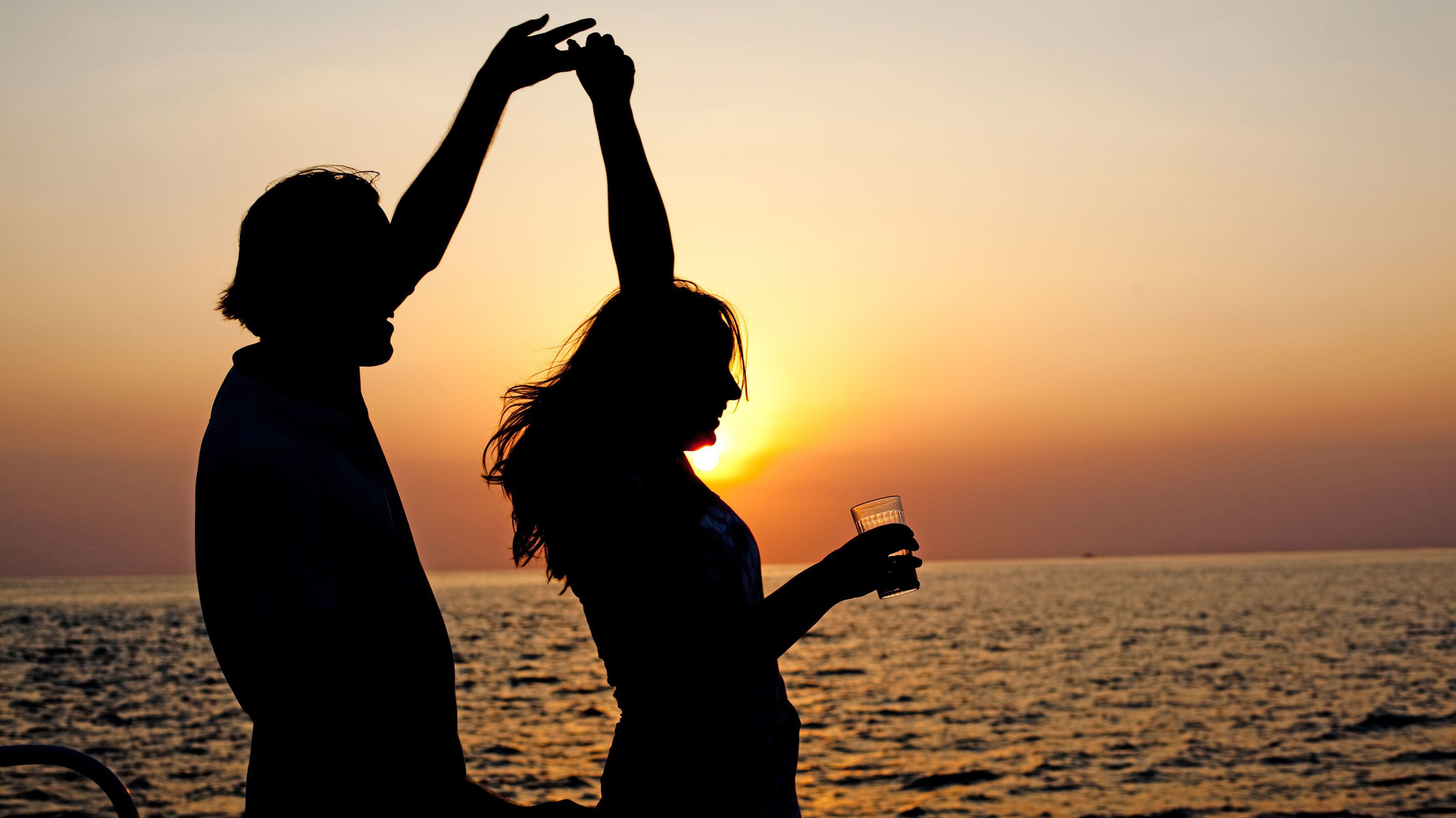 Couple dancing in the sunset aboard the Couple enjoying the Twilight Sunset Catamaran Cruise in the Turks & Caicos Islands