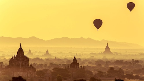 Foggy view of two hot air balloons floating over Bagan
