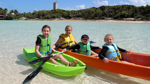 Mother and three kids in two kayaks on the water in the Bahamas