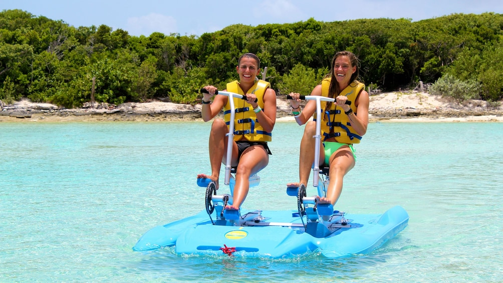 Show item 2 of 6. Two women ride a pedal-powered raft on the water in the Bahamas