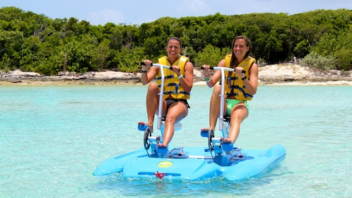 Two women ride a pedal-powered raft on the water in the Bahamas