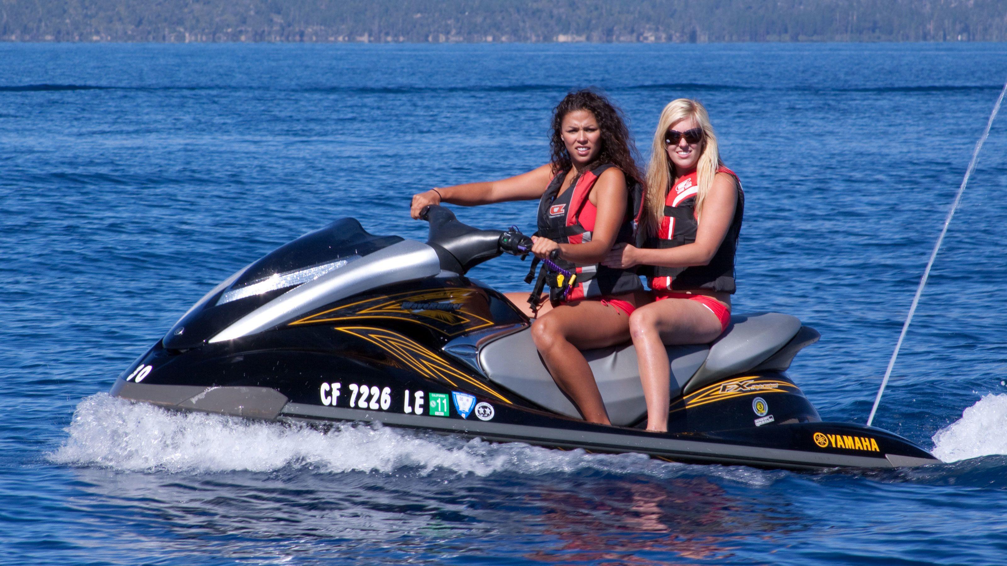 Two women sharing a jet ski in Lake Tahoe