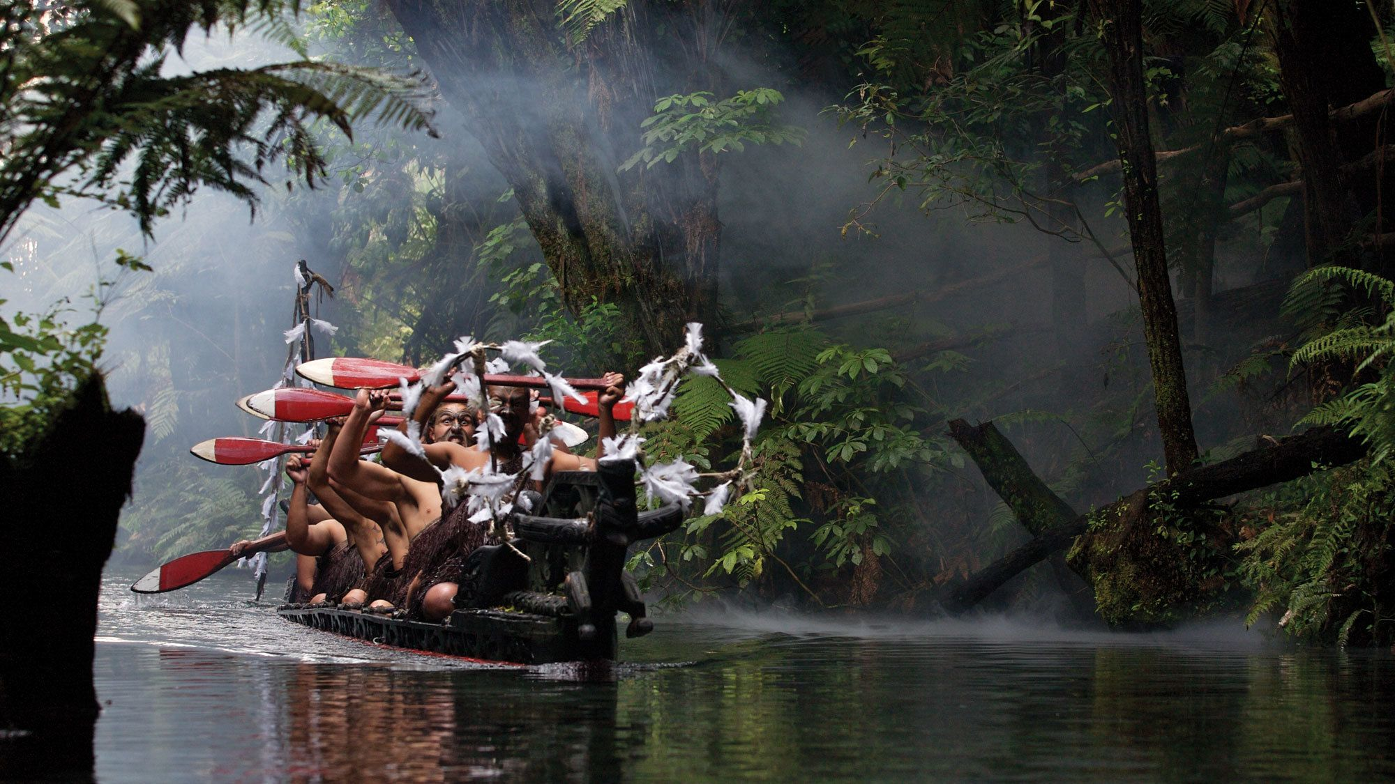 tribespeople rowing a small wooden raft in New Zealand