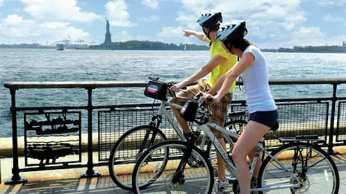 Two bicyclists looking out at the Statue of liberty from Brooklyn