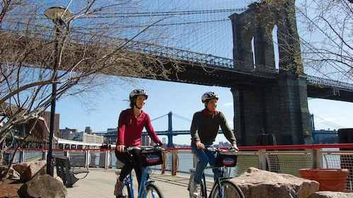 Couple riding their bicycles under the Brooklyn Bridge