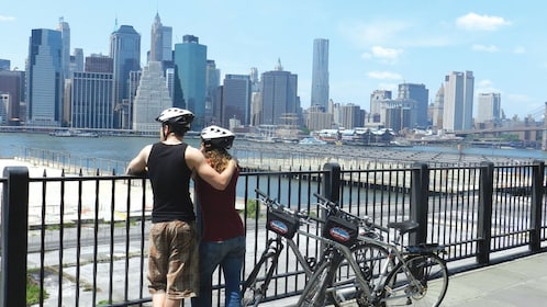 Two bicyclists looking out at the New York skyline
