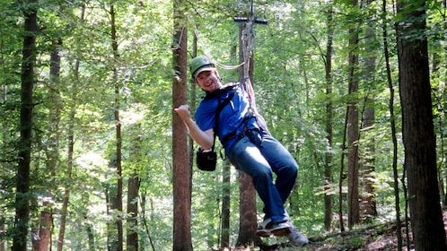 man ziplining through the woods in Indiana