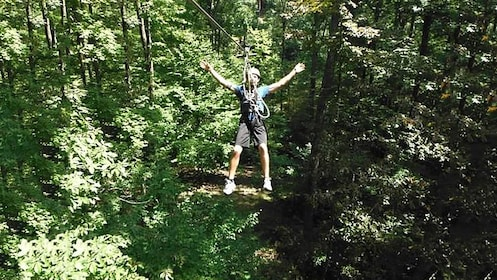 man goofing off while ziplining through the woods in Indiana