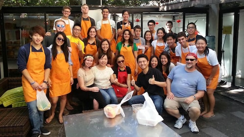 cooking class participants wearing orange aprons in Shanghai