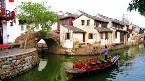 Man floating down the river in the Zhouzhuang Water Village