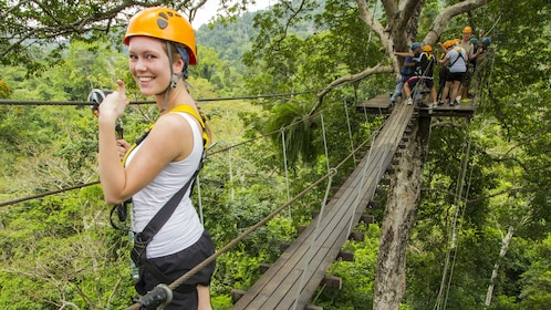 Young woman in foreground gives thumbs-up as she stands on zip line platform