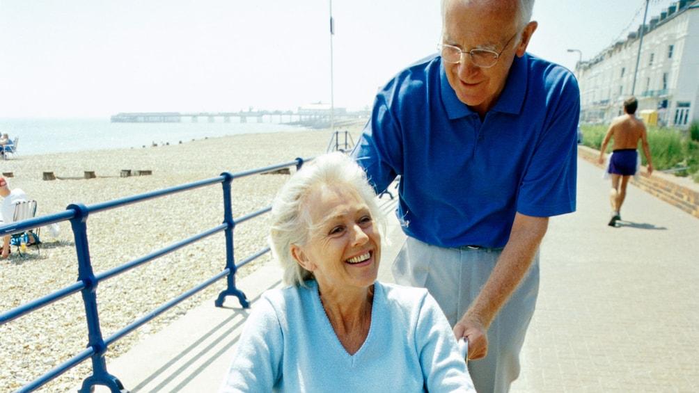 Show item 1 of 5. Man pushing woman in a wheelchair on a beachside boardwalk