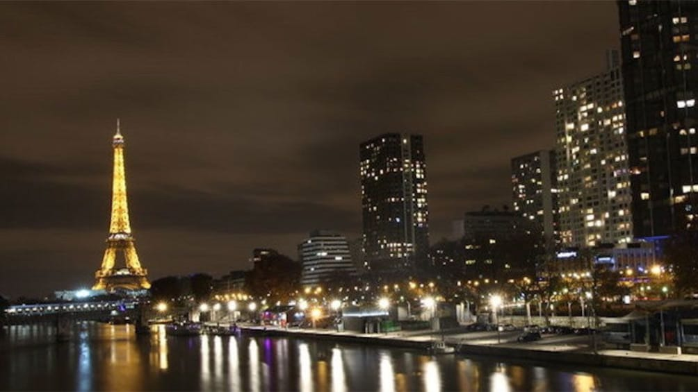 Charger l'élément 3 sur 5. Eiffel Tower and city along the riverbank lit up at night in Paris