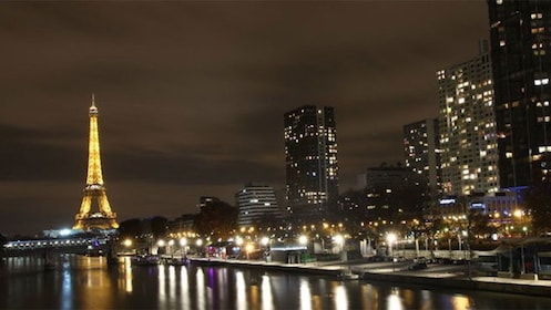 Eiffel Tower and city along the riverbank lit up at night in Paris