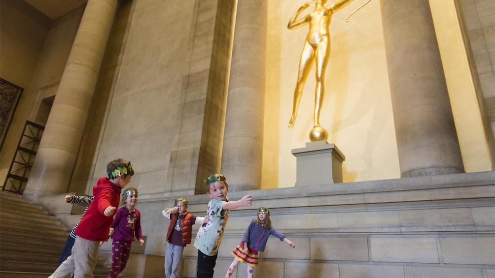 Children emulating a statue at the Philadelphia Museum of Art