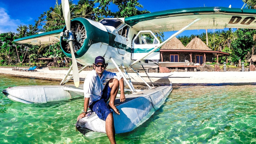 Show item 4 of 5. man sitting on float of plane in fiji