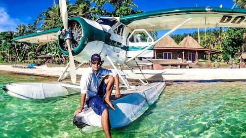 man sitting on float of plane in fiji