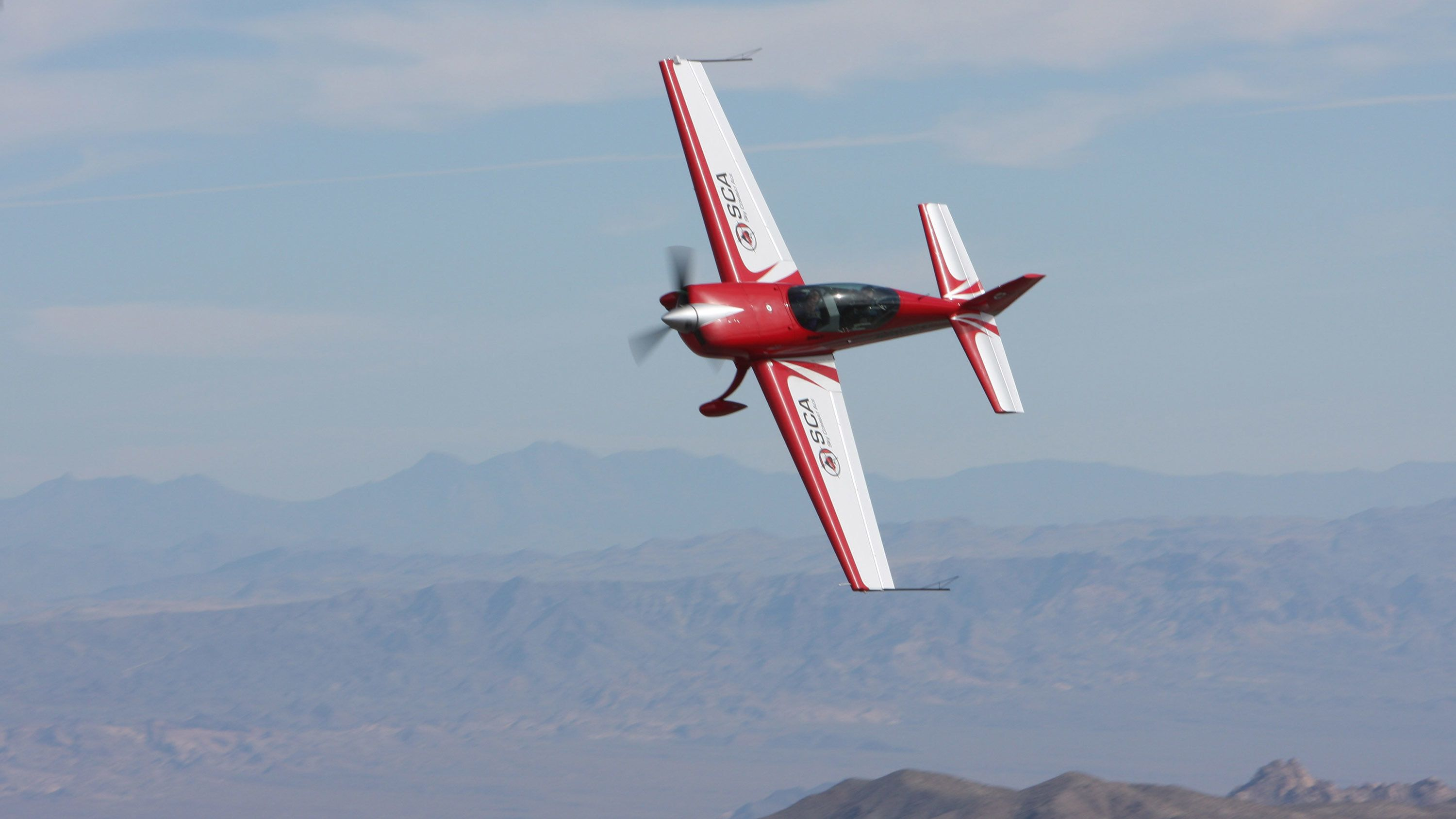 red plane making a sharp turn in the air in San Diego