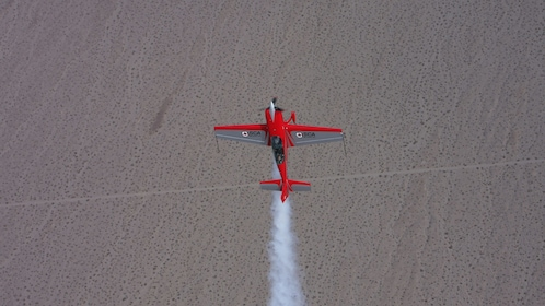 red plane ascending vertically in San Diego