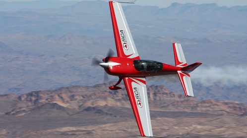 red plane taking a sharp turn in the air in San Diego