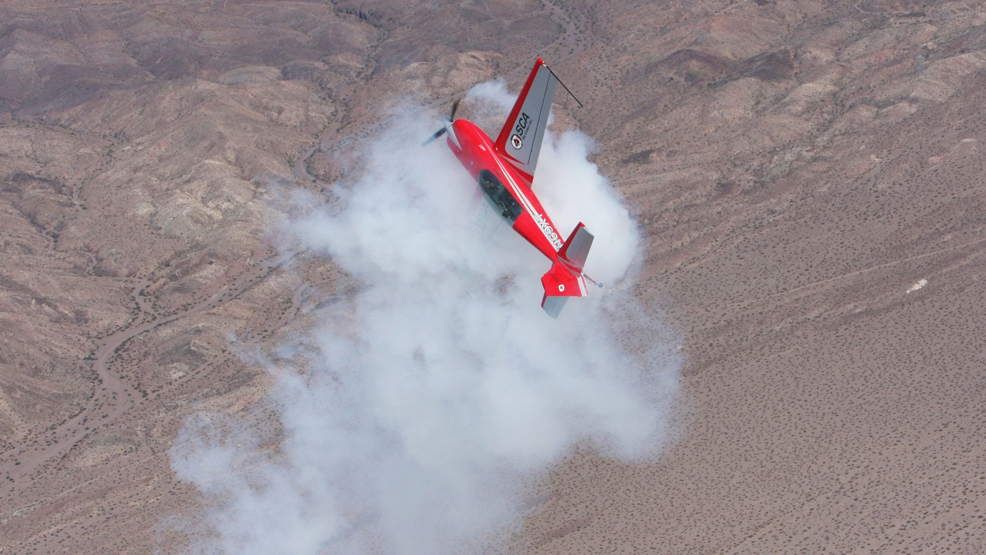 red plane performing a spiraling maneuver in San Diego