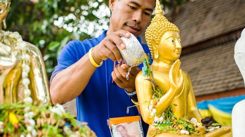 man washing temple relics in Thailand