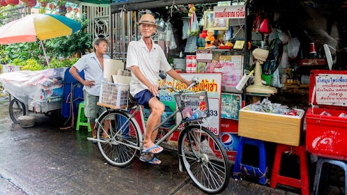 man on bicycle stopping by a convenience stand in Thailand
