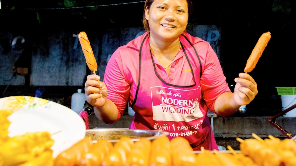 woman preparing hotdogs her food stand in Thailand