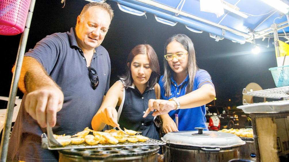 sampling street food in Thailand