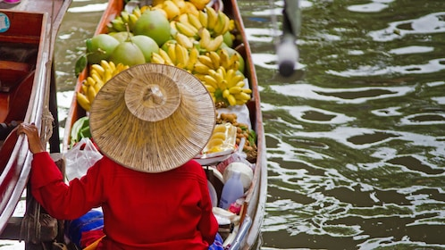person with boat full of bananas in bangkok