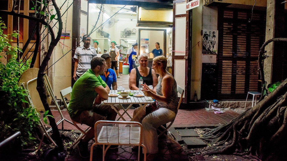 正在顯示第 4 張相片,共 5 張。 group enjoying street food at a small table outside in Thailand