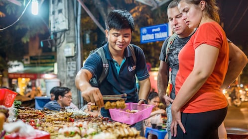 couple purchasing street food at the night market in Hanoi