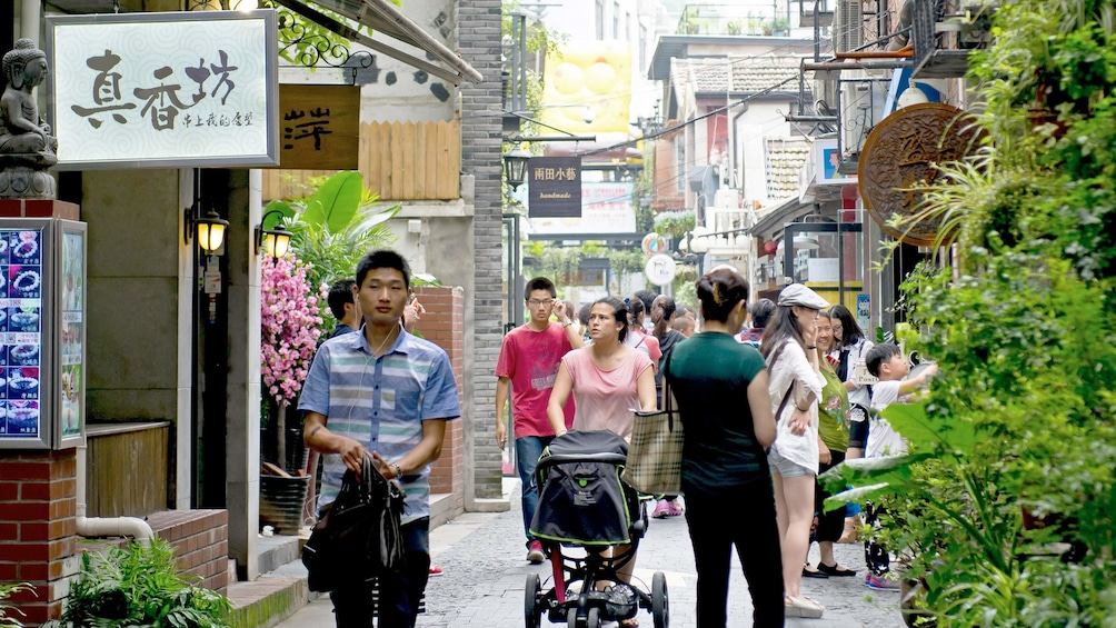 Show item 3 of 4. shoppers crowding the street in Shanghai