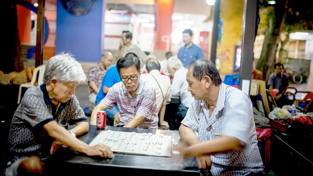 Charger l'élément 1 sur 4. Three men play a game in Hong Kong