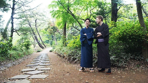 Two men stand near a wooded path in kimonos