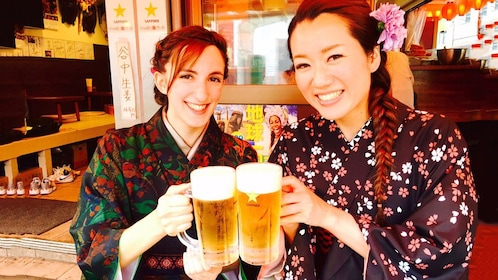 Two women pose in traditional Japanese costumes pose with beers