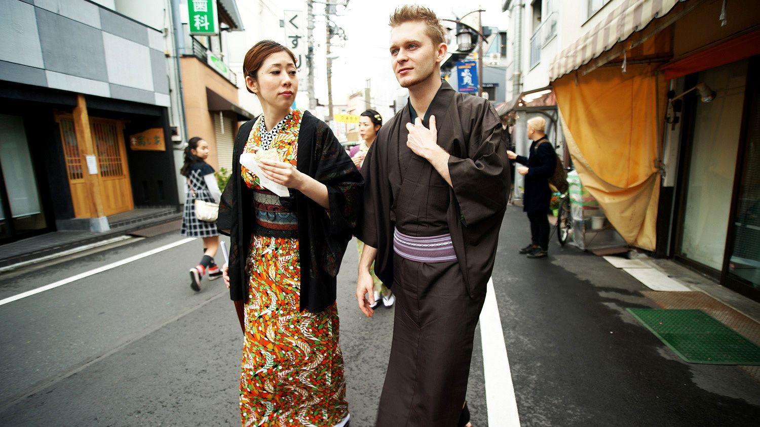 Man and Woman walk down the street in traditional Japanese costumes