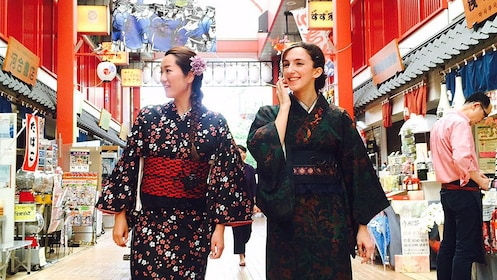 Two women clad in traditional Japanese costumes walk through market