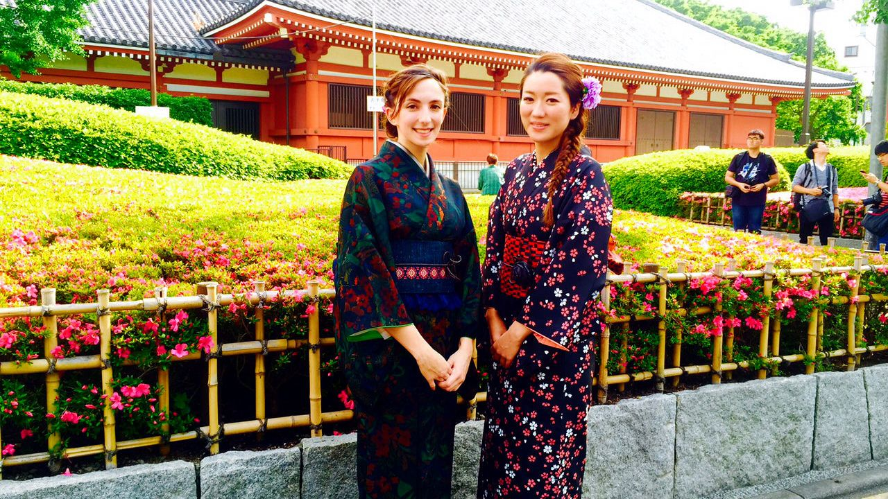 Two women pose in traditional Japanese costumes in a garden