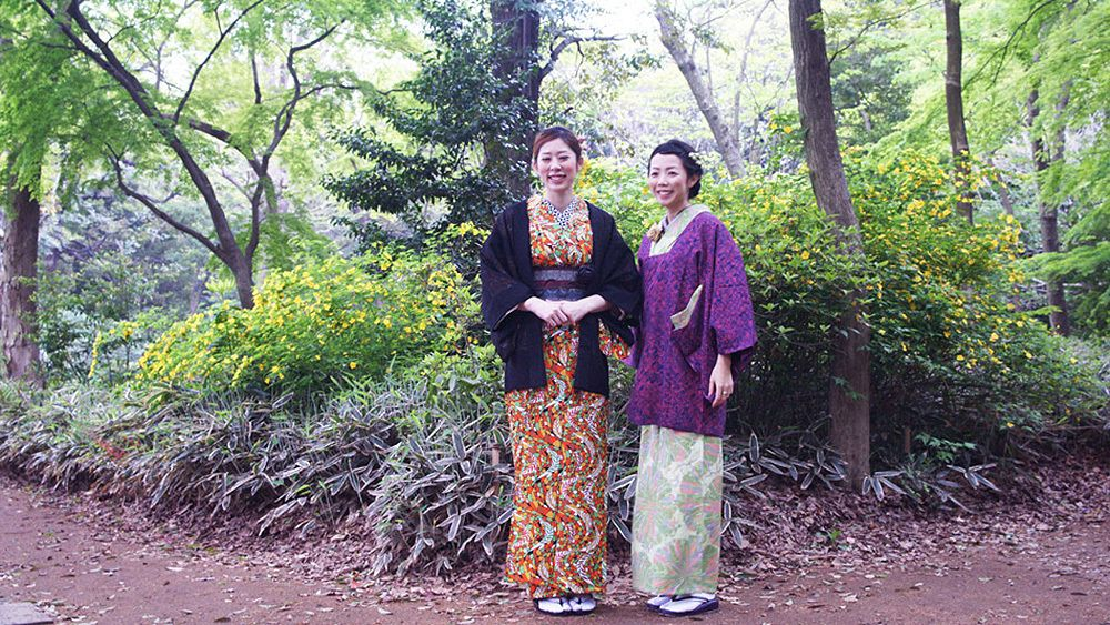 Two women pose in traditional Japanese costumes in nature