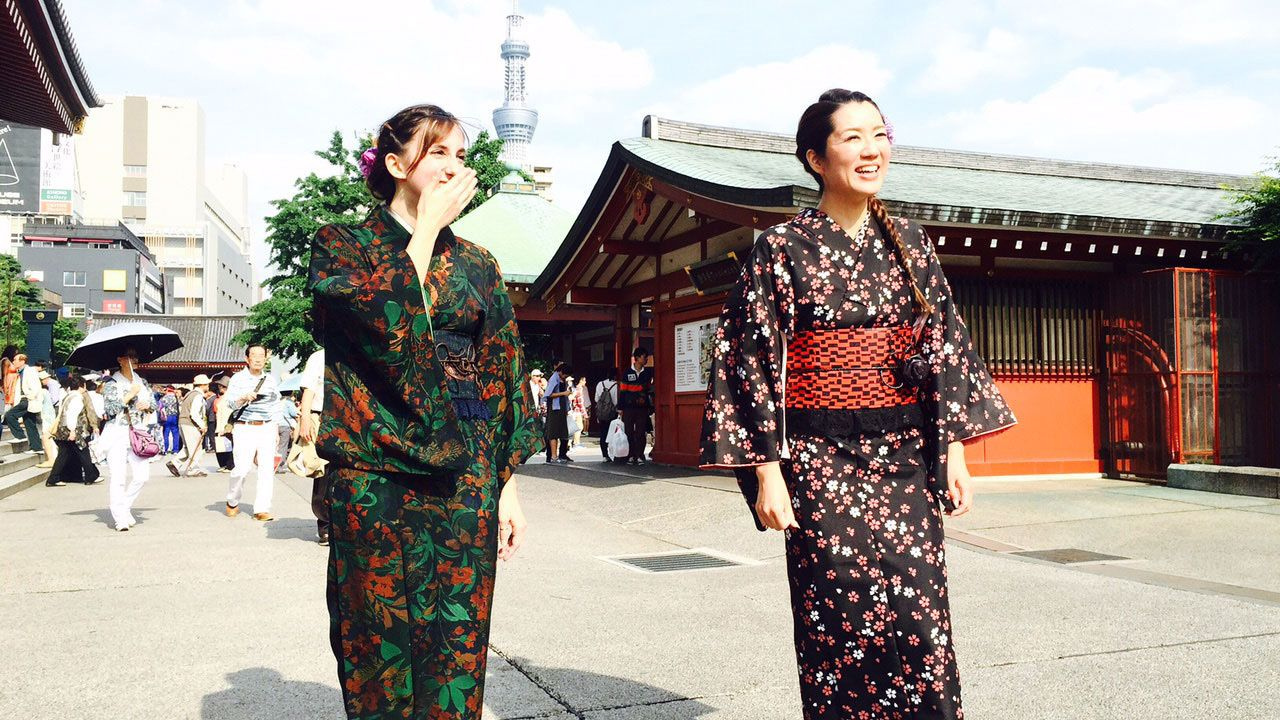 Two women pose in traditional Japanese costumes walk through a townsquare