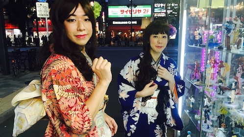 Two Japanese women in red and blue kimonos out at night in Tokyo.