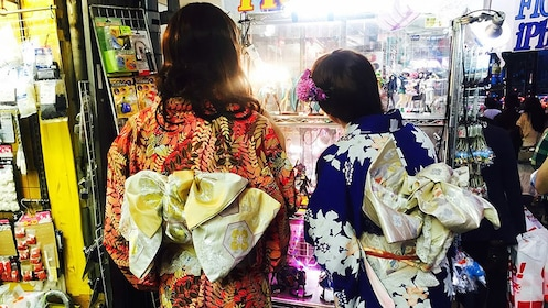 Two Japanese women in red and blue kimonos pictured from behind in Tokyo gift shop.