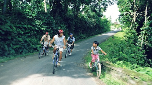 Group of bike riders riding through local village in Bali.